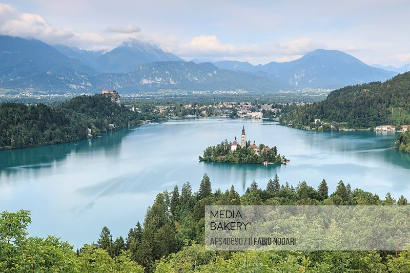Aerial view of lake Bled at sunset with a view of the island church and the castle.