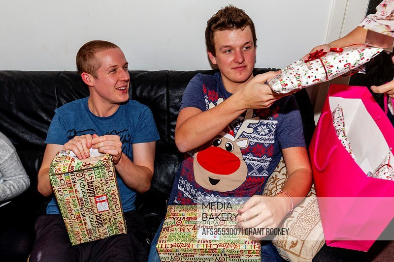 Young Men Opening Gifts On Christmas Day, Sussex, England.