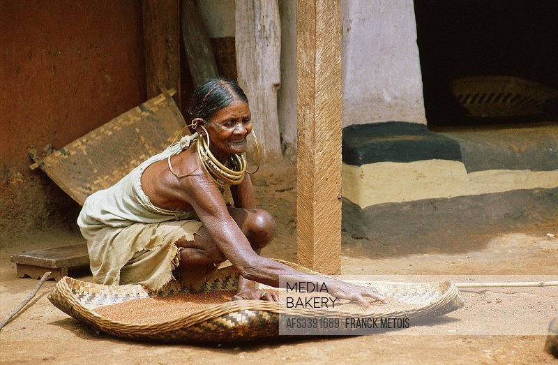A woman belonging to the Gadaba tribe is sun drying seeds. Orissa state India.