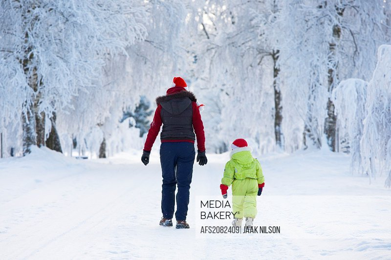 Three years old girl with mother in snowy parkway