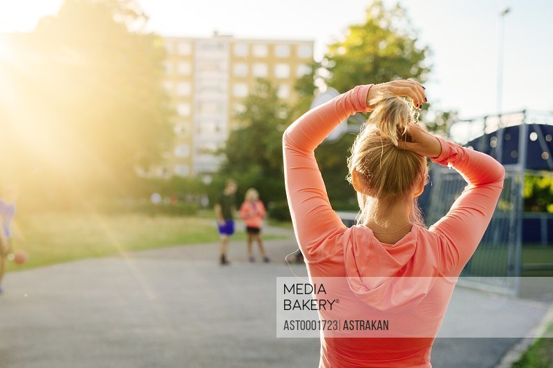 Rear view of sporty woman tying hair at basketball court