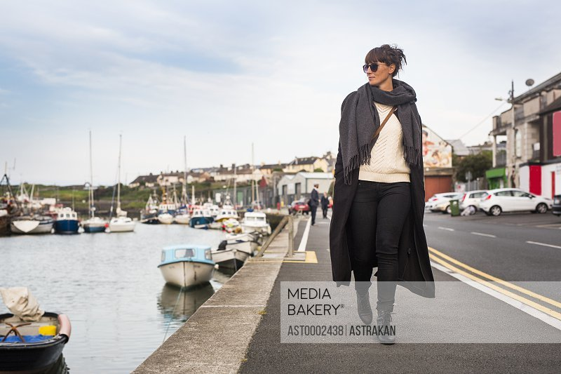 Full length of woman looking away while walking on road by harbor