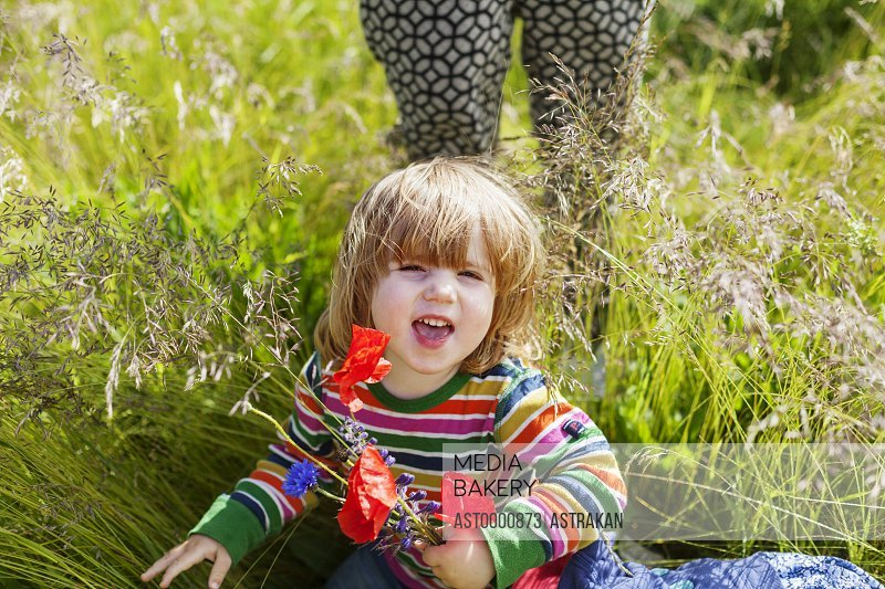 Girl holding poppy flowers and sitting at grassy field by woman
