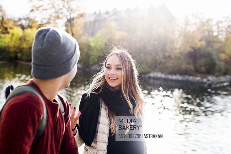 Young woman talking with male friend while walking by lake during winter