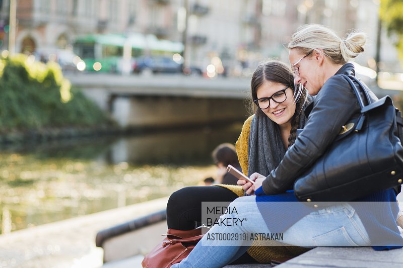 Mature woman showing smart phone on friend while sitting on steps