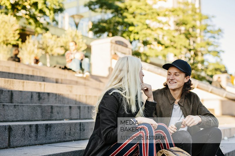 Low angle view of happy friends sitting on steps