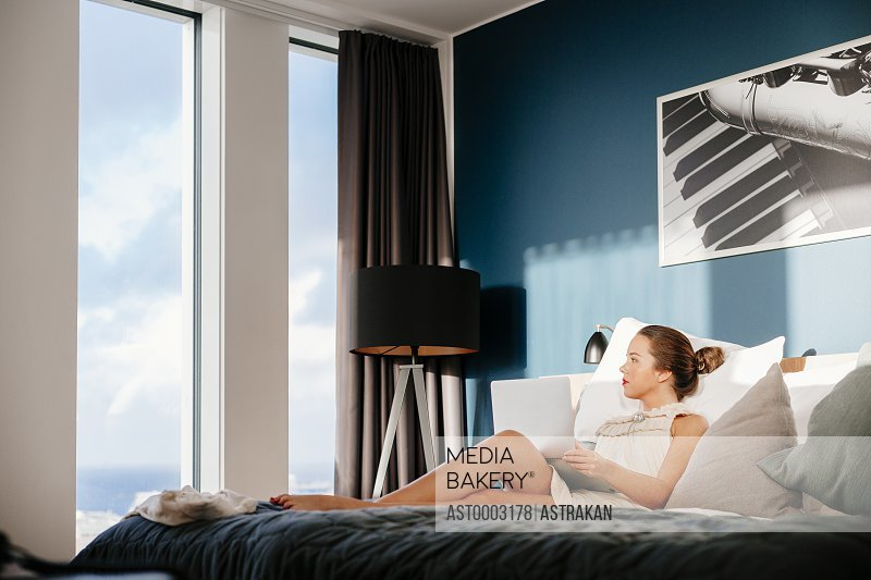 Businesswoman relaxing on bed while looking through window at hotel room