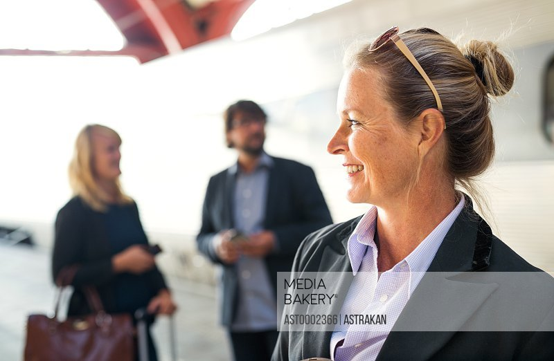 Happy businesswoman standing at railroad station with colleagues in background