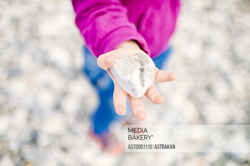 Girl holding pebble while standing on beach
