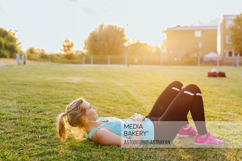Side view of sporty woman relaxing on grass at park