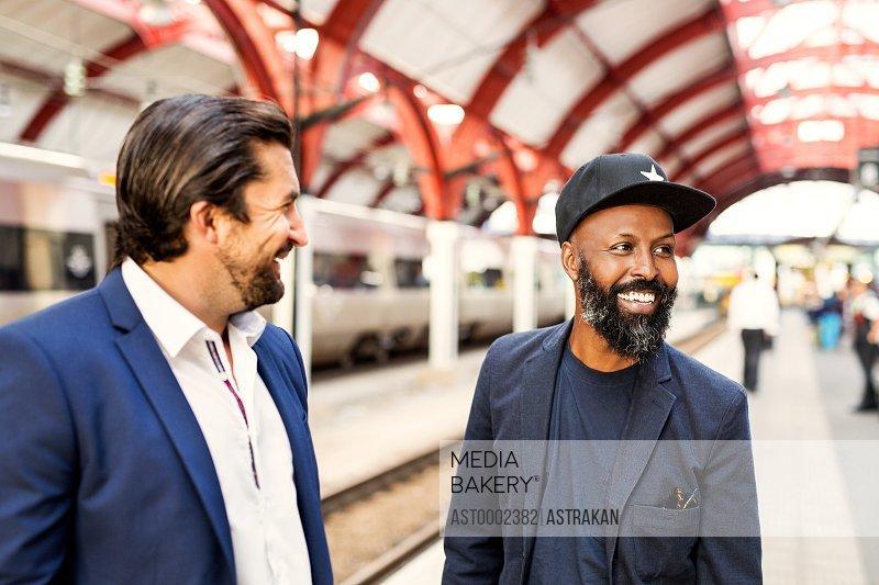 Happy businessmen at railroad station