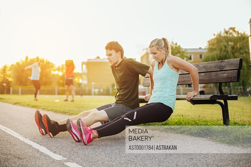 Determined man and woman stretching on wooden bench at park
