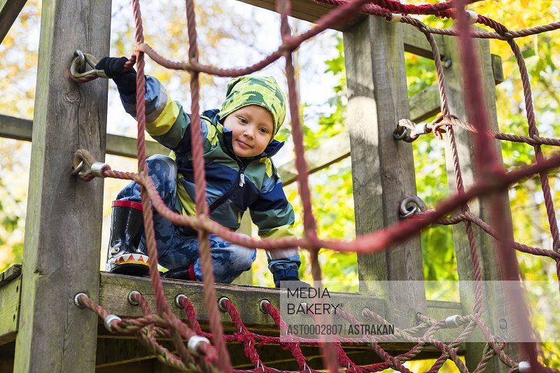Boy ready to enter rope net during obstacle course in forest