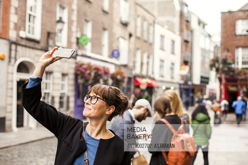 Smiling woman taking selfie with friends standing in background on city street