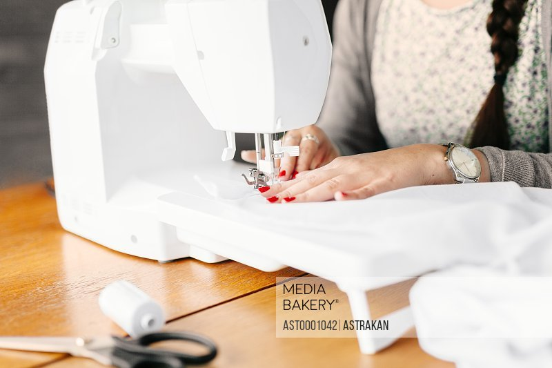 Midsection of design professional using sewing machine at table in studio