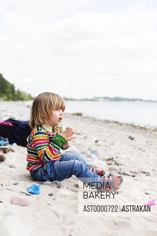 Close-up of girl sitting on beach and drinking juice