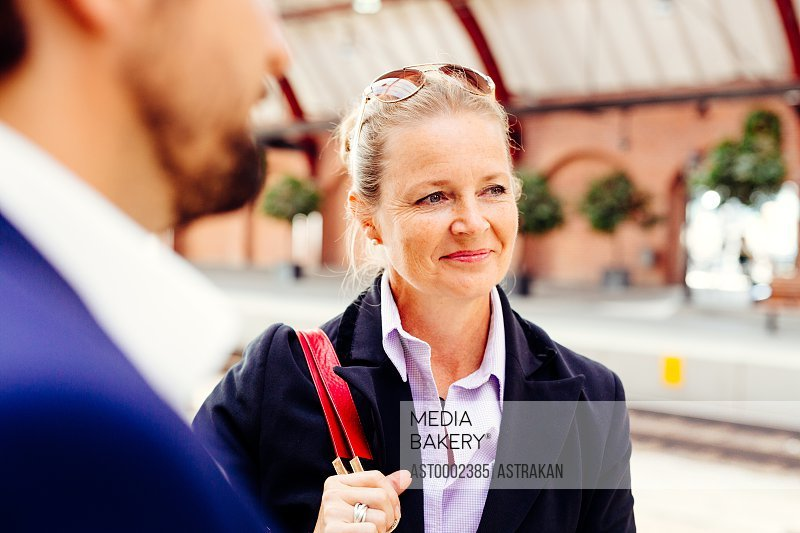 Thoughtful businesswoman standing with colleague at railroad station
