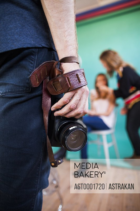 Midsection of photographer holding digital camera while fashion models getting dressed in background at studio
