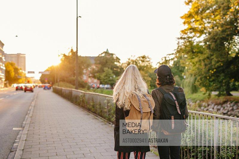Teenage friends walking on footpath in sunny day