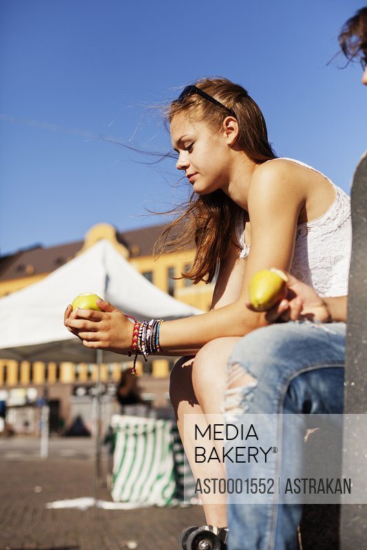 Girls holding apple while sitting at retaining wall