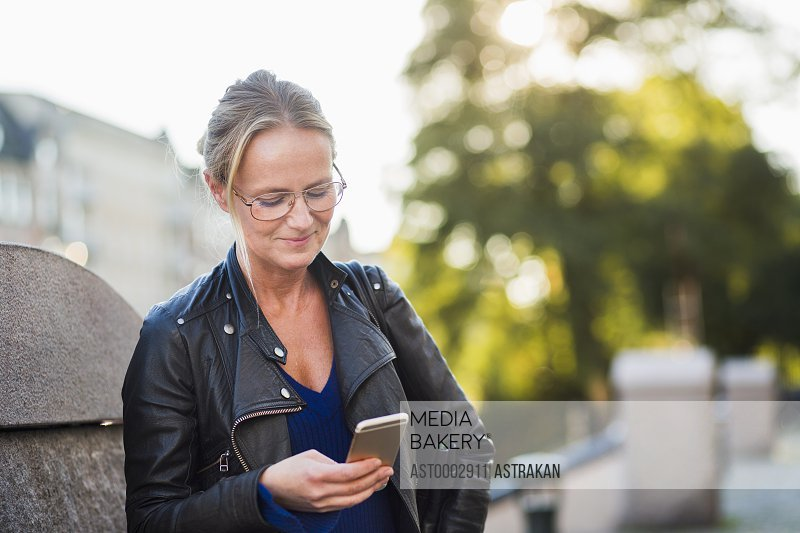 Mature woman looking at smart phone and smiling at street