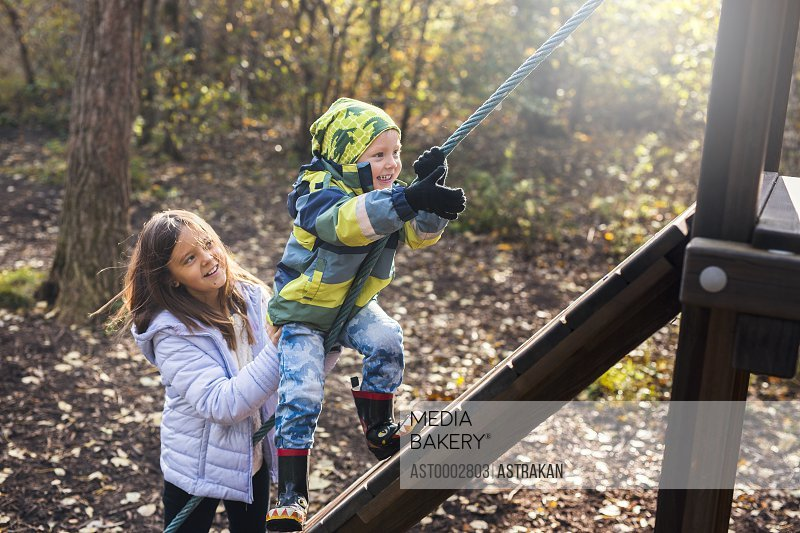 Girl assisting brother in climbing up obstacle wall at forest