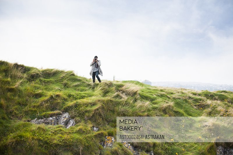 Man photographing while standing on grassy hill against sky