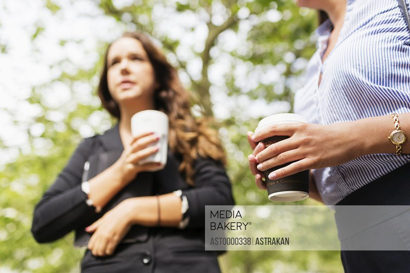 Low angle view of businesswoman holding coffee outdoors