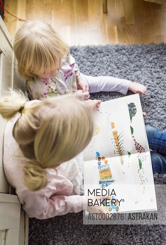 High angle view of sisters reading book while sitting on carpet at home