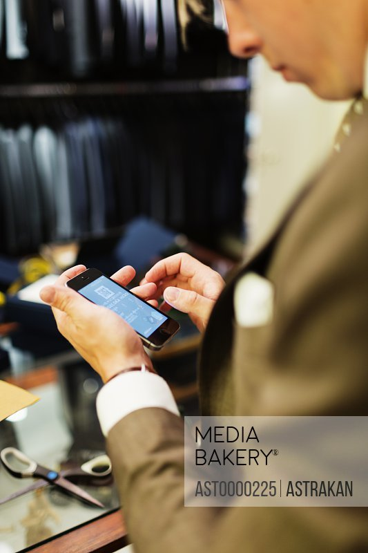 Young salesman using smart phone in clothing store
