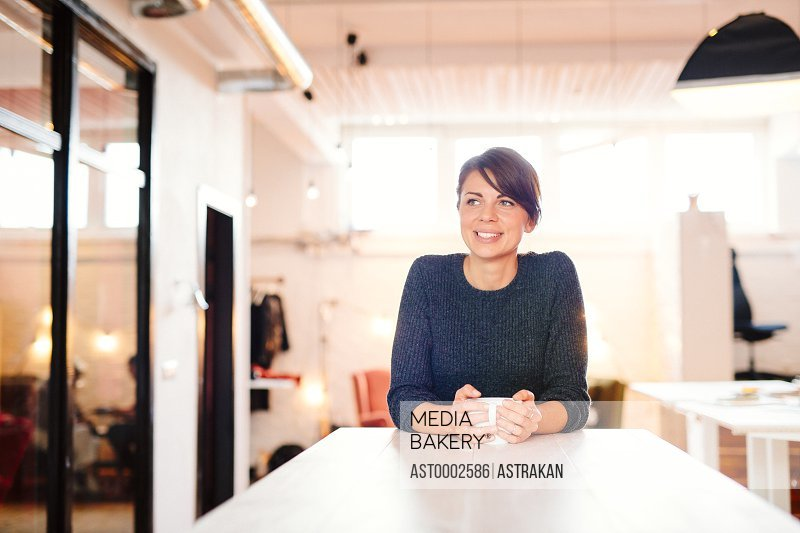 Smiling businesswoman looking away while holding coffee mug at desk in office