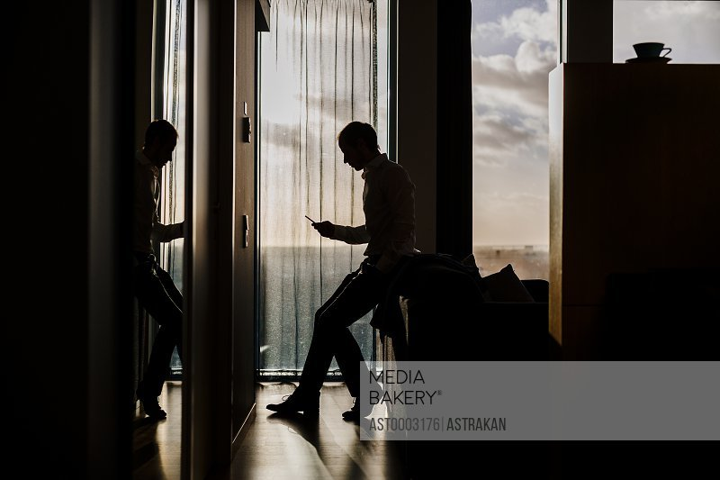 Side view of businessman leaning on sofa by window at hotel room