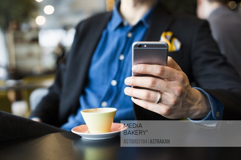 Midsection of businessman using smart phone with coffee at table