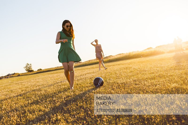 Young women playing football at garden