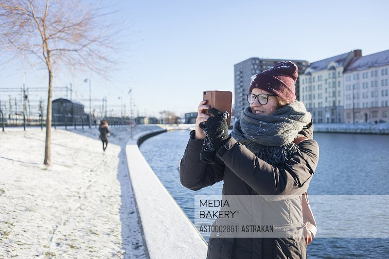 Happy woman photographing through smart phone by canal in city during winter