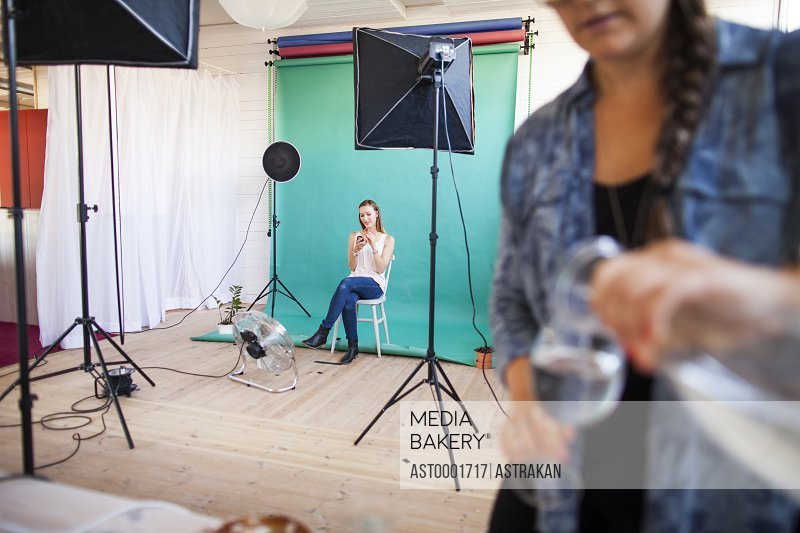 Photo assistant pouring water in glass while fashion model getting dressed in background at studio