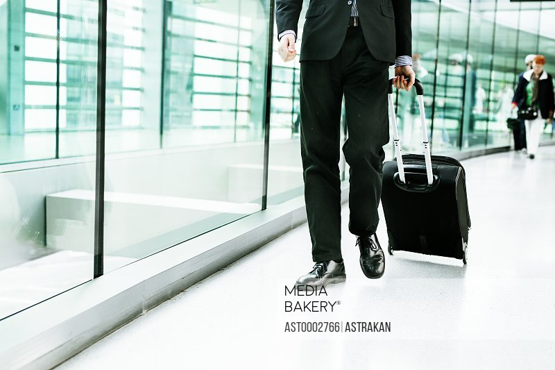 Low section of businessman walking with luggage at airport