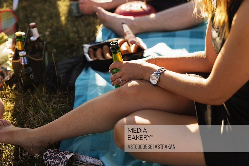 High angle view of woman holding beer bottle while sitting on field