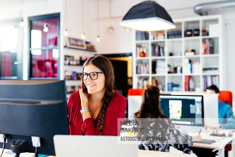 Smiling businesswoman using smart phone at computer desk in office