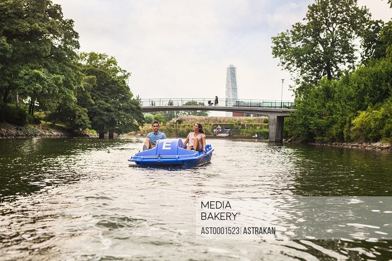 Couple pedal boating on river against bridge in city