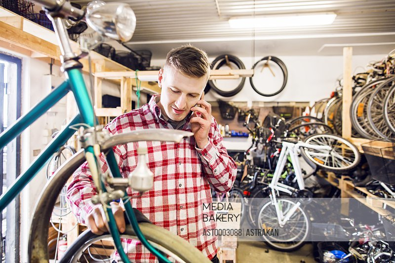 Mechanic using mobile phone while working in bicycle shop