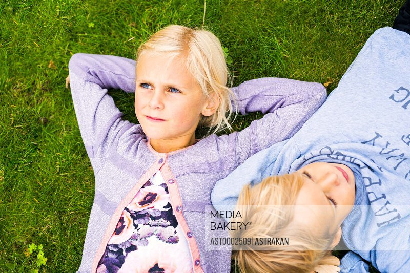 Directly above shot of girl with brother lying on grass in yard