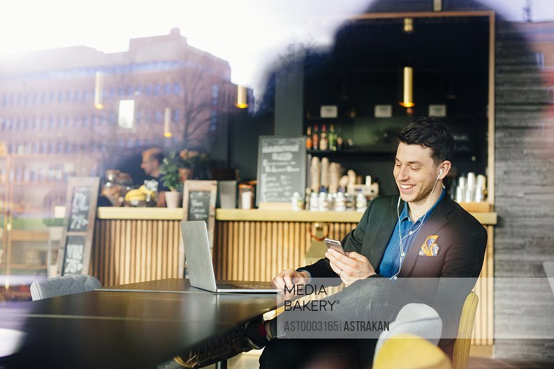 Smiling businessman listening to music while sitting with laptop at restaurant