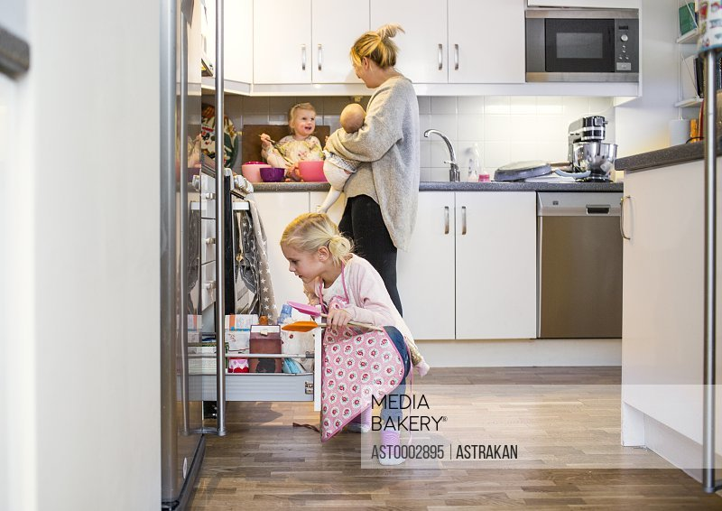 Girl searching in drawer while mother carrying baby in kitchen