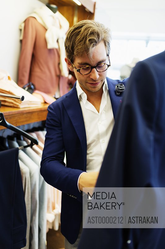 Handsome fashion designer working in clothing store