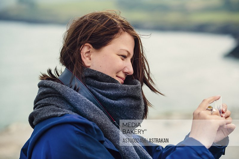 Side view of smiling woman holding smart phone on beach