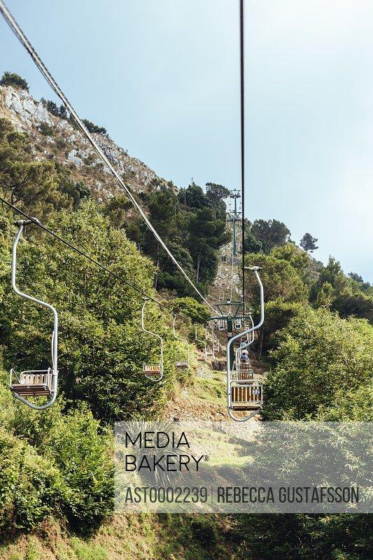 Ski lift over mountain against sky