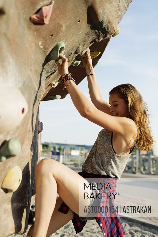 Side view of teenage girl climbing up artificial rock