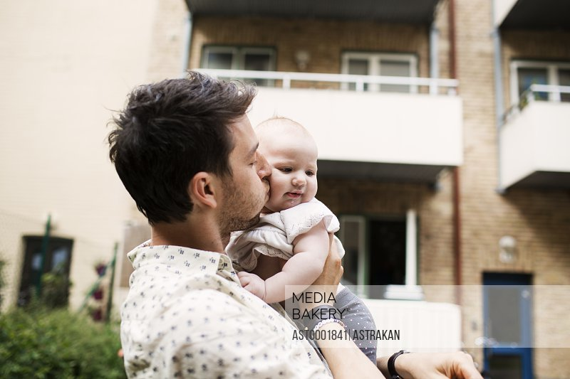Loving father kissing baby girl outside building