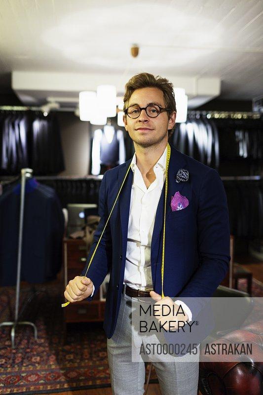 Portrait of handsome designer holding tape measure around neck in showroom